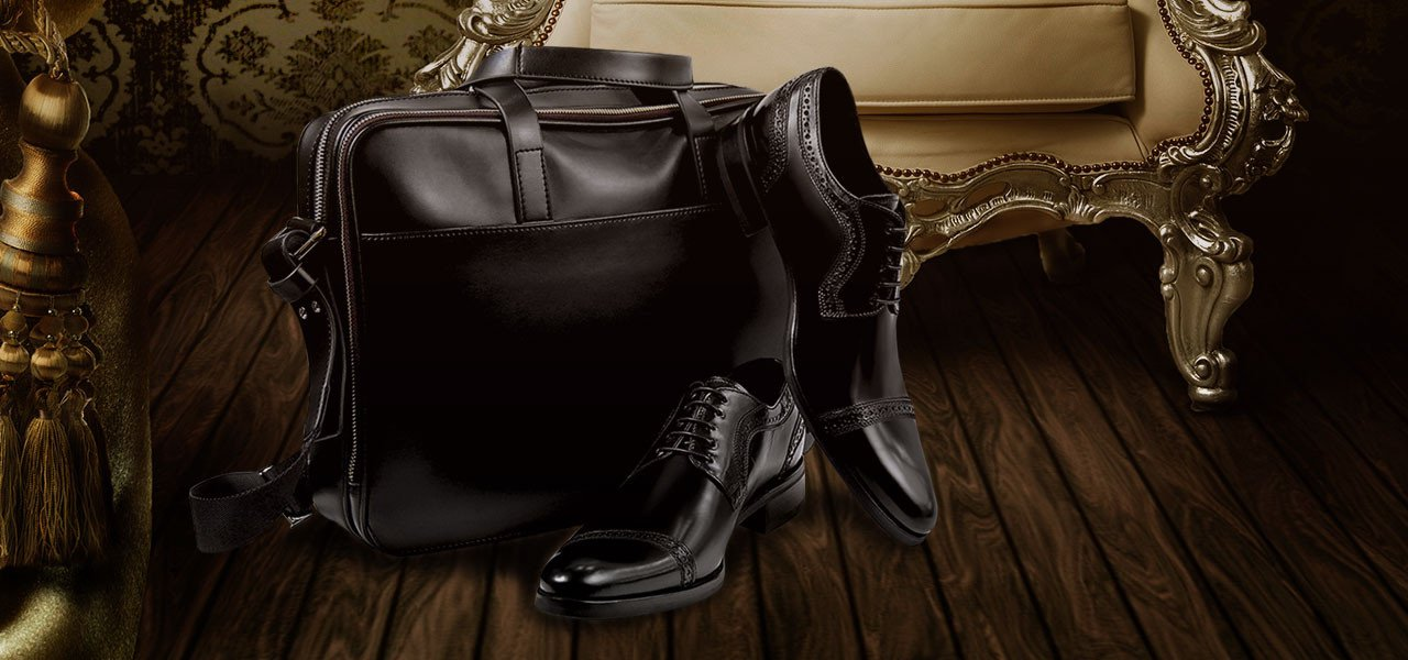 Black leather shoes with sling bag on wooden ground